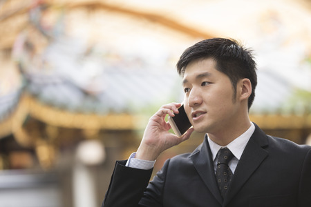 chinese temple: Chinese business Man using his cell phone outdoors with Chinese heritage temple in background. Stock Photo