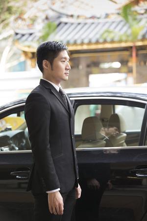 Asie chauffeur ou homme d'affaires debout à côté d'une voiture de luxe. Temple du patrimoine chinois à fond.