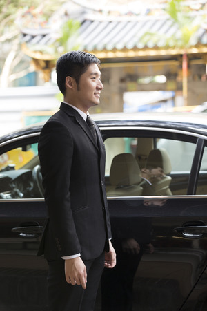 Chauffeur: Asian chauffeur or business man standing next to a luxury car. Chinese heritage temple in background.