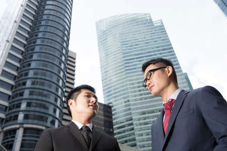 two visions: Two Chinese business men in modern Asian city. Asian businessman smiling & looking at the camera with skyscraper office buildings above.