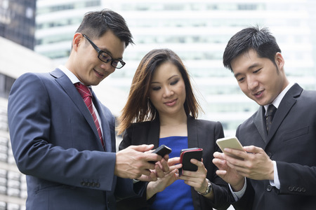 Group of Chinese business colleagues using mobile phone's outside the office. Stock Photo - 28540837