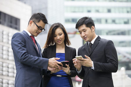 Group of Chinese business colleagues using mobile phones outside the office. photo