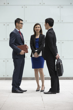 Happy Chinese Business colleagues outside the office talking to each other. photo