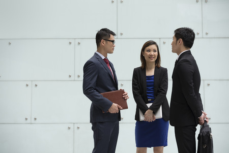asian business people: Happy Chinese Business colleagues outside the office talking to each other. Stock Photo