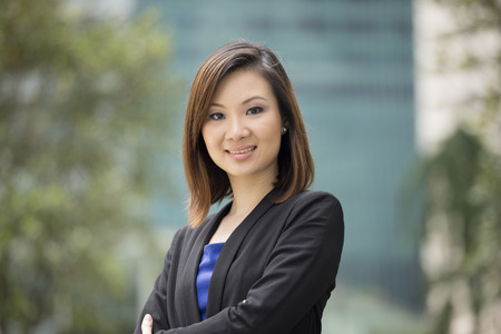 Portrait of a beautiful Chinese businesswoman in smart business suit. Asian business woman standing outside in modern city.