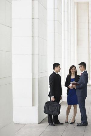 caminar: Colegas de negocios chinos felices fuera de la oficina hablando el uno al otro.