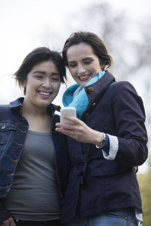 Two female friends looking at a smartphone outdoors in the city. Asian and Caucasian technology and lifestyle concept.  photo