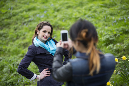 Portrait of two young women taking pictures of themselves through cellphone. Caucasian and Chinese friends taking photo with phone. photo