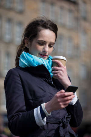 Happy young woman on cell phone outside in City. Beautiful caucasian woman holding coffee cup and using smartphone. photo