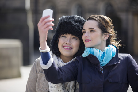 Two happy women, friends taking self portrait with their phone Camera Outdoors. Caucasian and Chinese friends taking photo with phone. photo