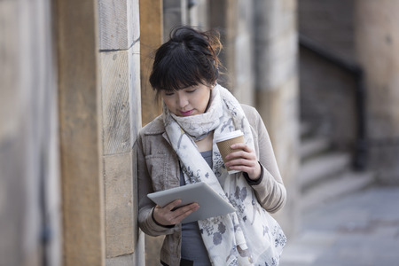 Young Chinese woman using a tablet pc outside and leaning against a stone wall. photo
