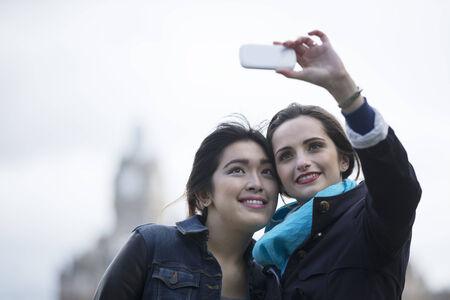 Due donne felici, amici prendendo autoritratto con la fotocamera del telefono esterna. Amici caucasici e cinesi tenendo foto con il telefono. photo