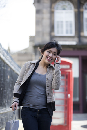 Chinese woman talking on smartphone holding shopping bags by red phone booth in Edinburgh, United Kingdom.  photo