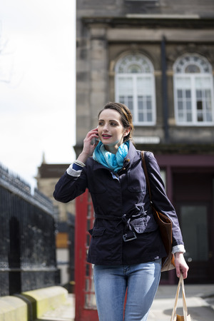phonebox: Happy young woman on mobile phone outside an Englsih Red Phonebox. Beautiful caucasian woman using smartphone. Stock Photo