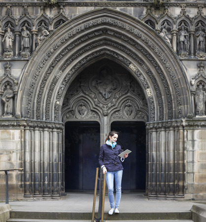 Young caucasian tourist with her tablet standing near a Cathedral in Edinburgh, Britain. photo