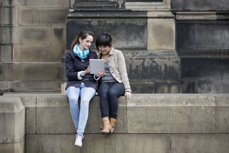 Two female friends looking at a tablet pc outdoors in the city. Asian and Caucasian technology and tourism concept.  photo