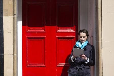 red door: Modern Caucasian woman, using digital Tablet standing next to a red door. Beautiful young professional European businesswoman. Caucasian ethnicity.