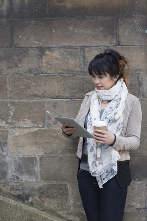 stone tablet: Young Chinese woman using a tablet pc outside and leaning against a stone wall.