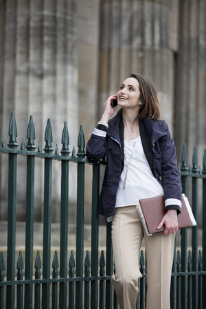 Modern Caucasian Business woman, talking on mobile smart phone outside. Beautiful young professional European businesswoman. Caucasian ethnicity. photo