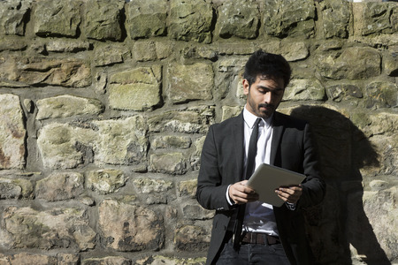 stone tablet: Indian man with a tablet computer. Asian business man using digital tablet computer, leaning against a wall.