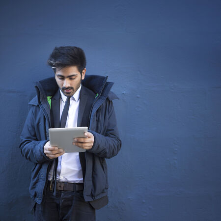 Indian man with a tablet computer. Asian business man using digital tablet computer, leaning against a blue wall. photo