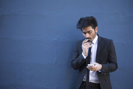 Indian man with a smartphone & cigarette. Asian business man using smartphone, leaning against a blue wall. photo