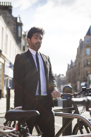 Retro style Indian man with Bicycle in the City. Student or young business man commuting photo