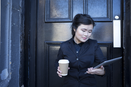 Modern Chinese Business woman, reading Tablet PC outside on a break standing next to a black door. photo