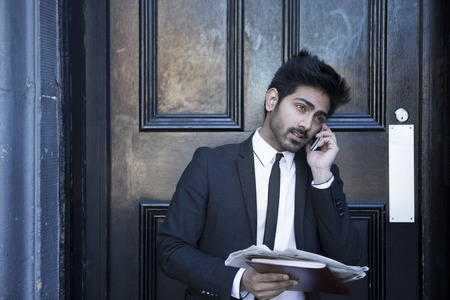 A Indian man in a business suit takes a phone call while holding a newspaper. Urban man standing outside a black door. photo