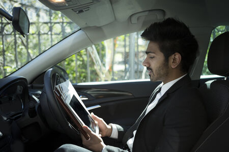 Indian businessman sitting in his parked car and using Tablet PC. photo