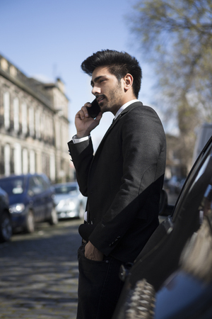 Indian businessman standing outside his car and talking on mobile phone. photo