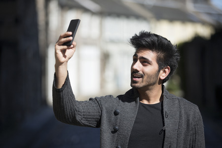 Young Indian Man standing in city street taking a selfie, self-portrait photograph with mobile phone. Background is blured city. photo