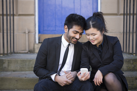 Two Asian business people sitting outdoors using smartphone. Young urban couple hanging out and using tech in the city. photo