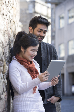 Two Asian friends sitting outdoors using digital Tablet. Young urban couple hanging out and using tech in the city. photo