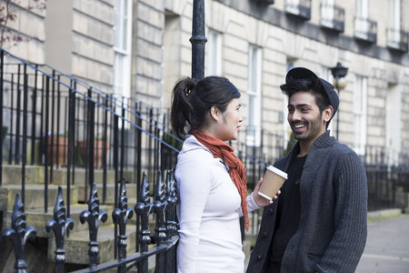 Two Asian friends  standing outdoors talking. Young urban couple hanging out in the city Stock Photo