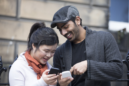 Happy Asian friends using mobile phone outside in street. Young urban couple hanging out in the city using tech. photo