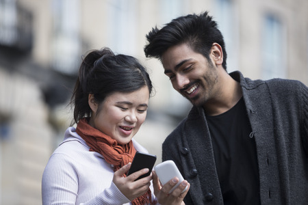 Happy Asian friends using mobile phone outside in street. Young urban couple hanging out in the city using tech.
