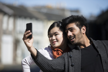 Happy Asian friends using mobile phone to take selfie self-portrait photograph. Young urban couple hanging out in the city using tech. photo