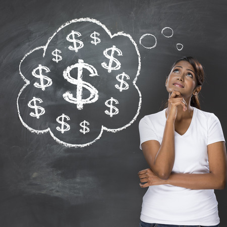 Indian woman thinking about money. She is standing under a thought bubble containing $ signs drawn on a dark chalkboard.