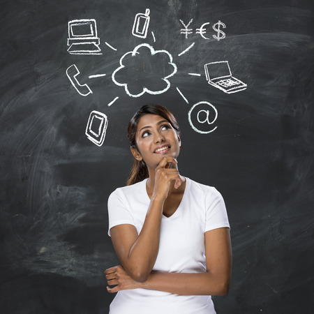 Happy Indian woman in front of Cloud computing symbols drawn on chalkboard. photo