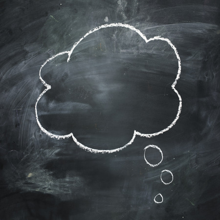 Hand drawn thought bubble on a dark dark chalkboard. Stock Photo