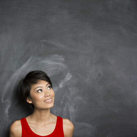 Happy Chinese woman standing in front of a dark chalkboard. The chalk board is blank waiting for a message. photo