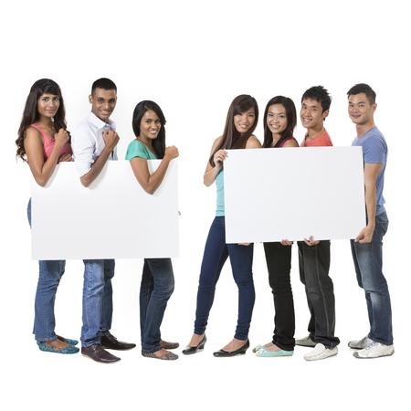 Deux Groupe de personnes asiatiques tenant une grande bannière pour votre message. Isolé sur fond blanc. Équipes indiennes et chinoises brandissant des pancartes. Banque d'images