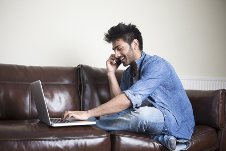 Asian Man using a laptop and talking on phone at home in the lounge. photo