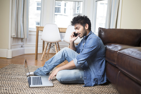 Asian Man using a laptop and talking on phone at home in the lounge.