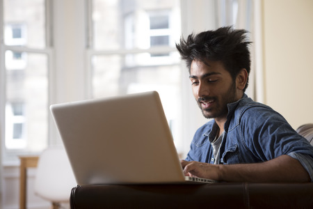 Asian man using Laptop at home in the lounge. photo