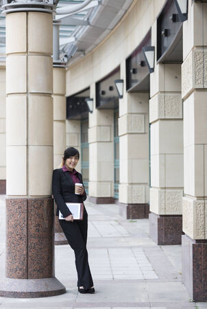 Professional Chinese businesswoman outside in modern city using a digital tablet PC. photo