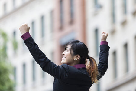 raised arms: Triumphant Chinese businesswoman with arms raised. Concept about an Asian business woman celebrating success. Stock Photo