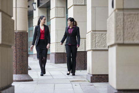 Two Businesswomen having an informal meeting outside a modern office building. Asian and Caucasian business women having a conversation. photo