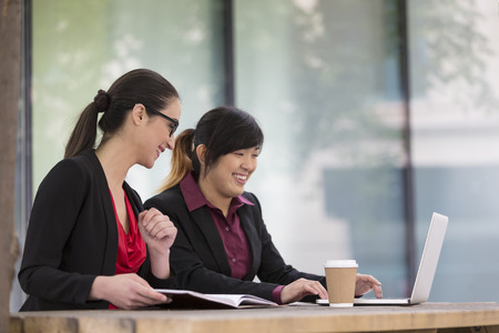 Two female Business women working on a laptop computer. Caucasian and Asian business colleagues at work. Banque d'images